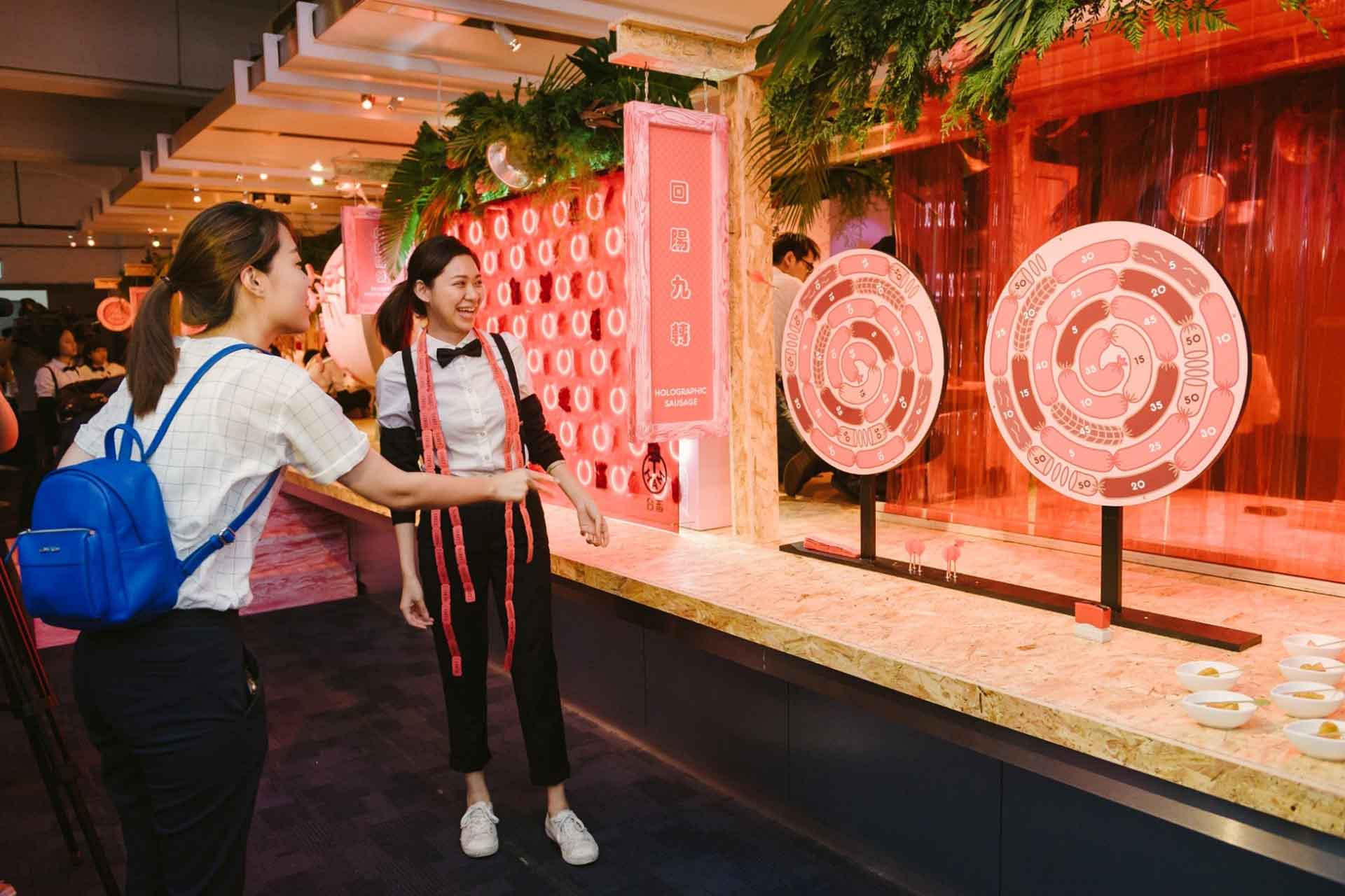 展場以熱鬧的臺灣傳統夜市為發想,還有類似夜市遊戲的趣味互動,圖為民眾體驗射飛鏢轉盤。