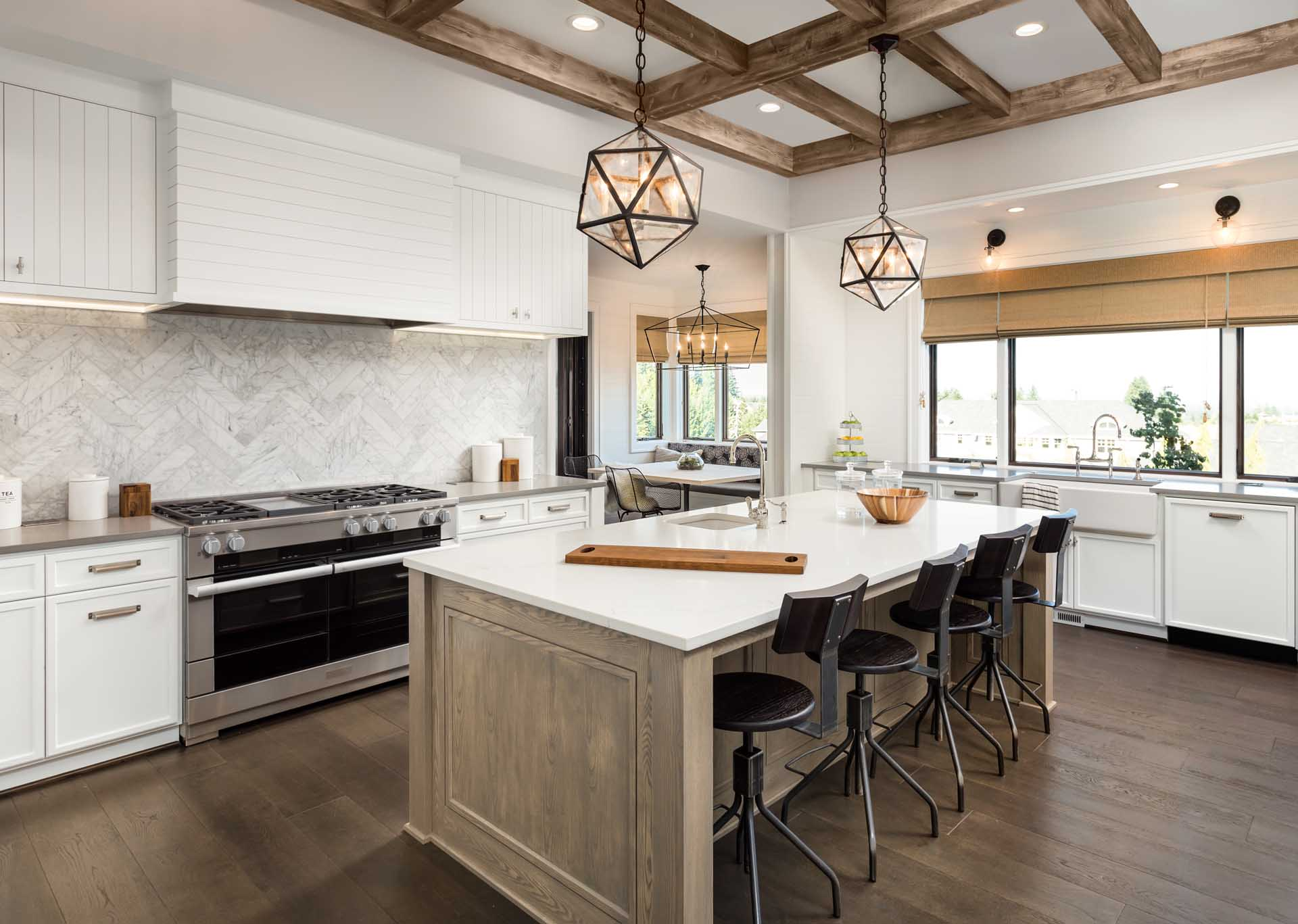 Kitchen Interior with Island, Sink, Cabinets, and Hardwood Floors in New Luxury Home. Features Elegant Pendant Light Fixtures, and Farmhouse Sink next to Window; Shutterstock ID 639915670; PO: 25pack; Job: 20180906; Client: tt; Other: aa